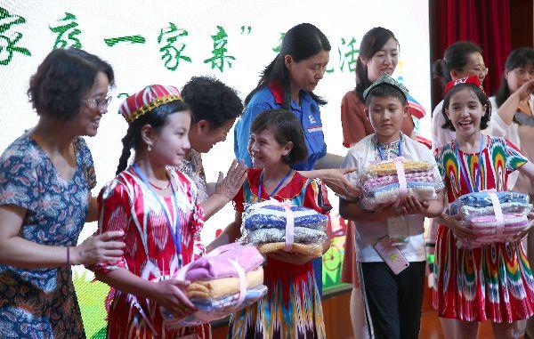 """北京的""""爱心妈妈""""向和田儿童赠送礼物."""